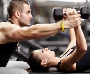 woman lifting weights with male personal trainer - Train Hard Fitness 8180 Oswego Rd. Liverpool, NY 13090 315-409-4764