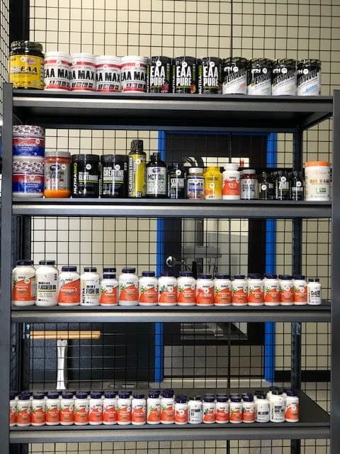 supplements on a shelf straight on - Train Hard Fitness 8180 Oswego Rd. Liverpool, NY 13090 315-409-4764