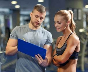 man and woman looking at a clipboard - Train Hard Fitness 8180 Oswego Rd. Liverpool, NY 13090 315-409-4764